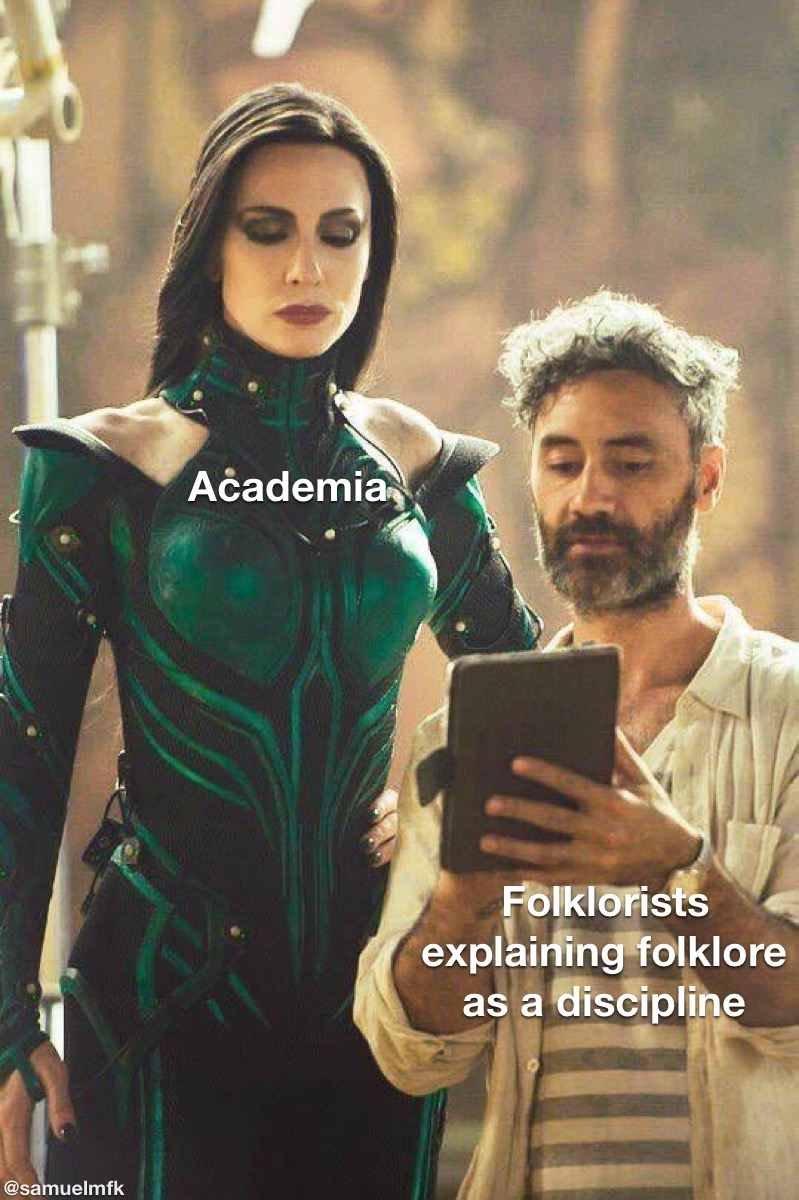 """An image of film director Taika Waititi giving actress Cate Blanchett notes on the set of Thor: Ragnarok. Blanchett is wearing a green bodysuit and is standing over Waititi who appears to be reading from a series of notes. Blanchett is labeled """"Academia"""" and Waititi is labeled """"Folklorists explaining folklore as a discipline"""" in white text."""