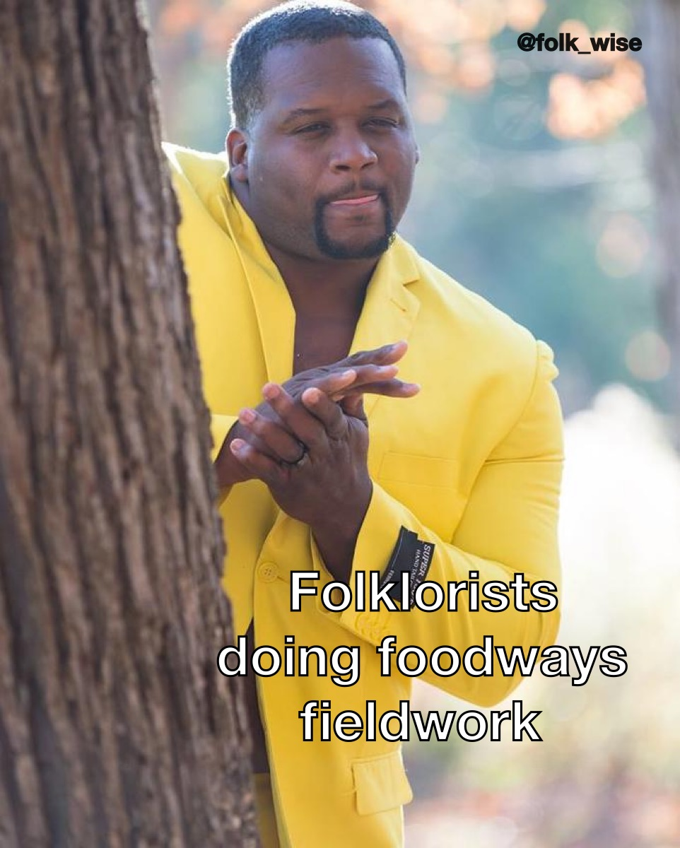 an image of Anthony Adams, a dark-skinned man wearing a circle beard and a bright yellow suit jacket, poking his head from around a tree with his tongue slightly out licking his lips and rubbing his hands together